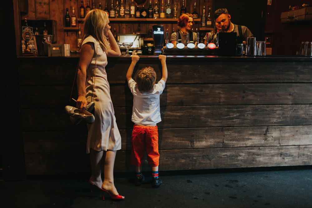 Toddler hangs of bar at wedding reception at Lock 91.