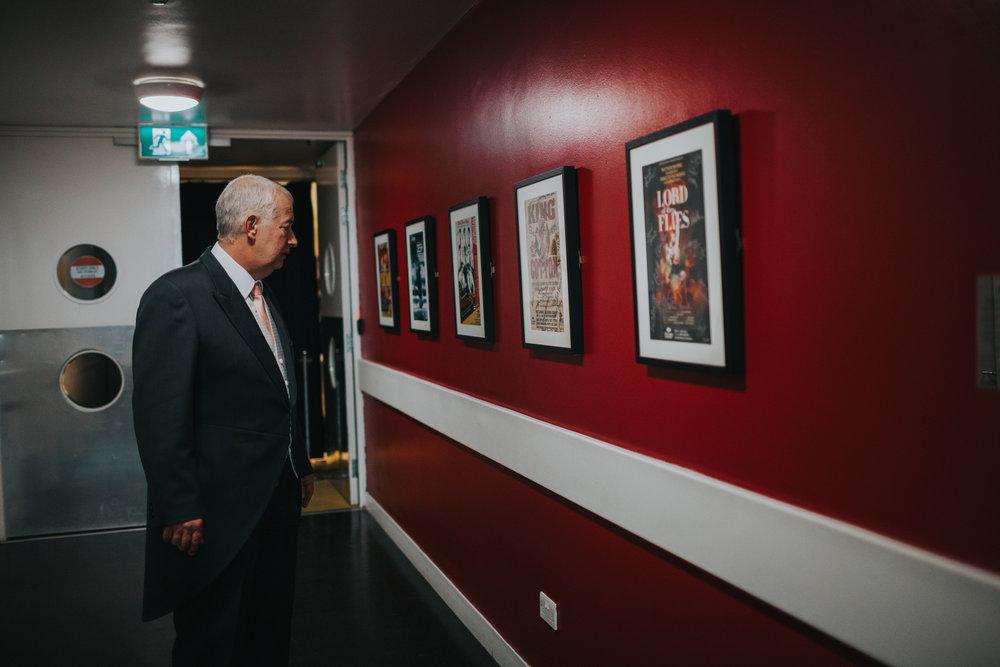 Wedding guest appreciates artwork in hall way.