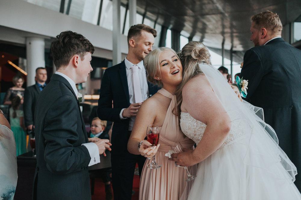 Bride hugs bridesmaid.
