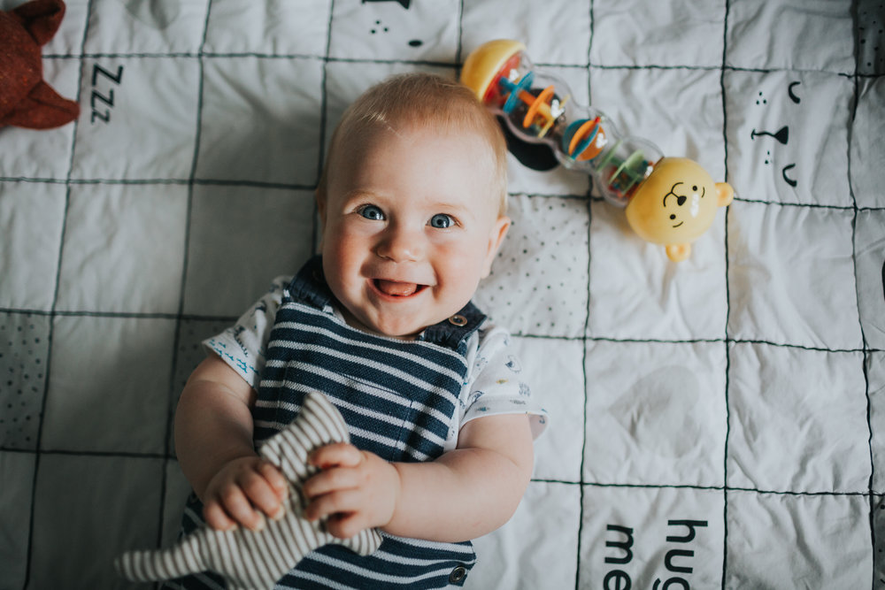 Baby giving the camera a big smile, holding his toy.