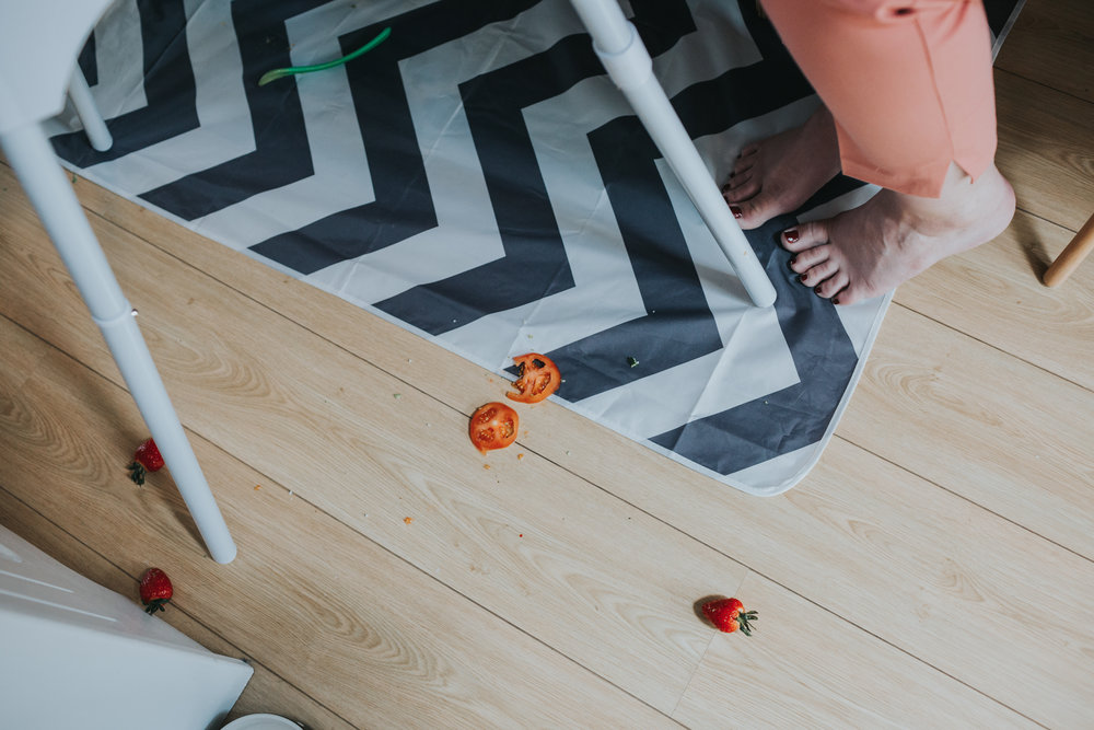 Tomato and strawberries on the floor near high chair.