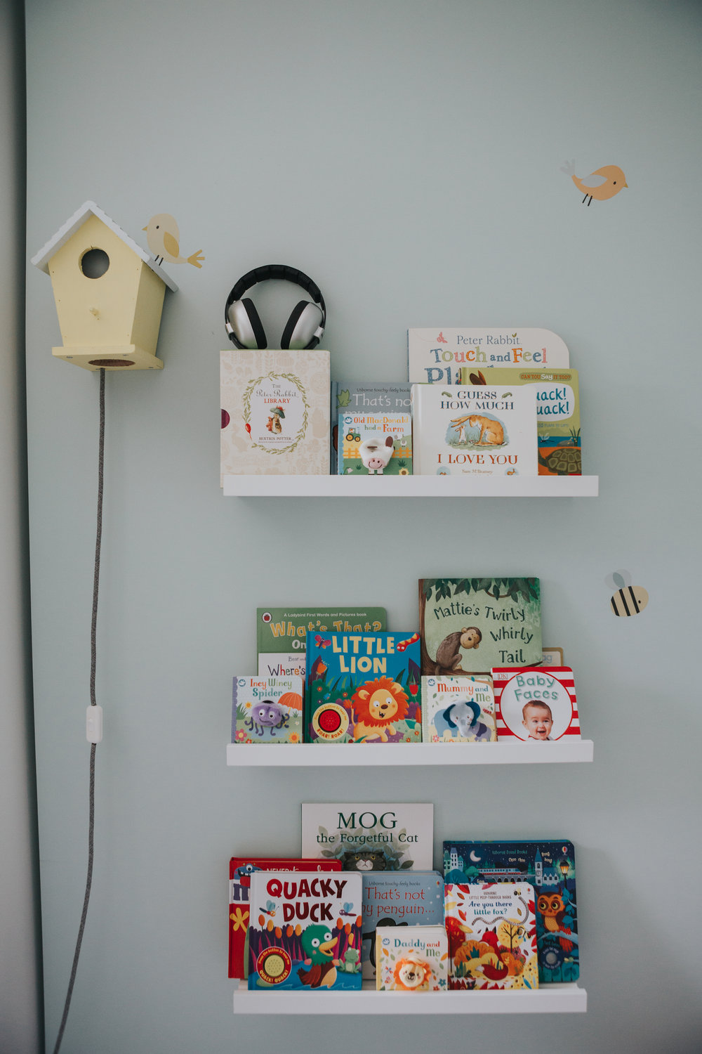 Bird house and book shelves in babies room.