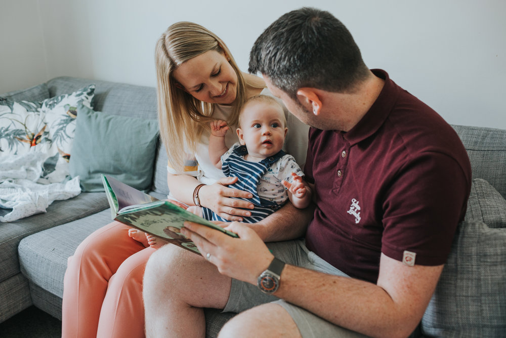 Baby looks proud at being able to read at 6 months old.