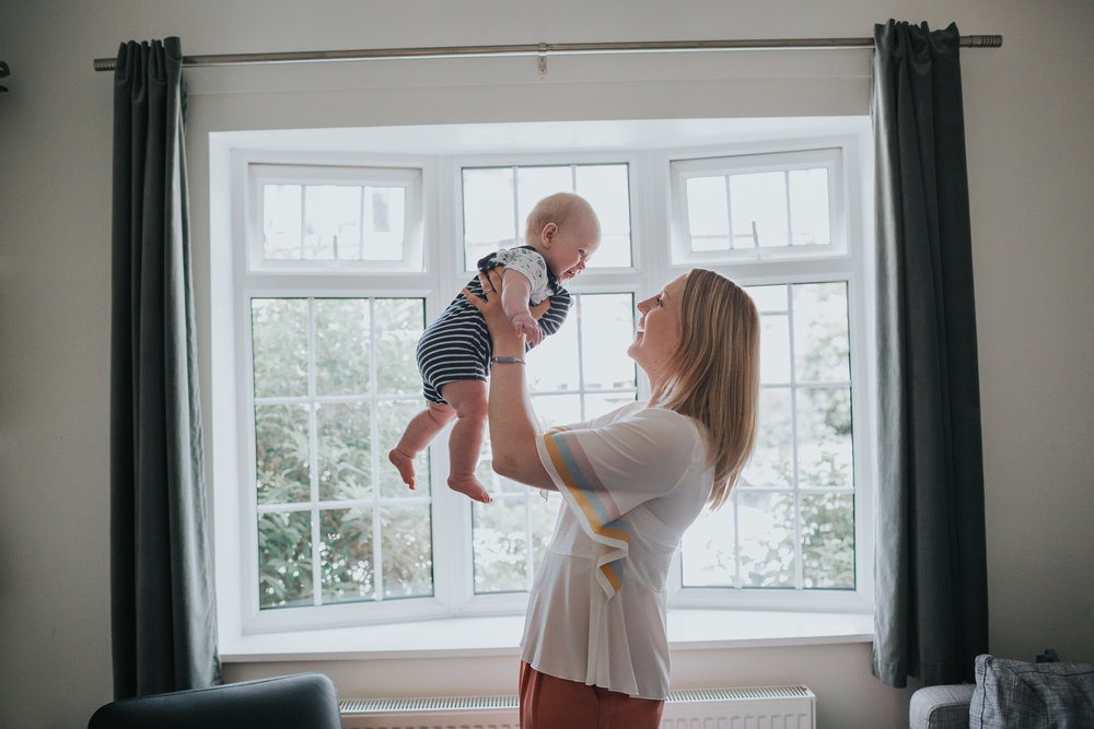 Mum chucks baby up and down in front of their living room window.