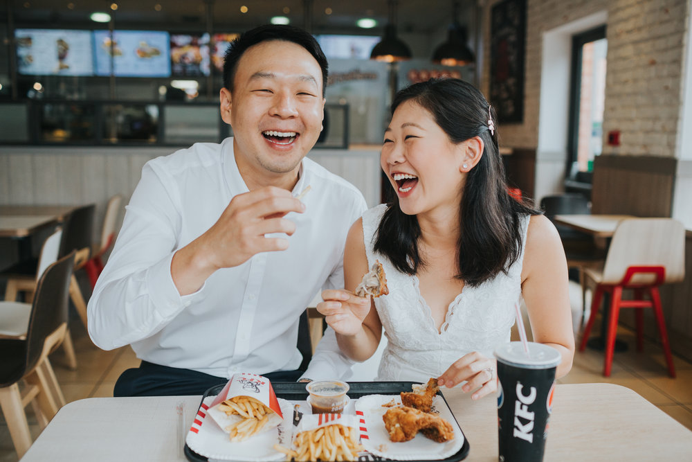 Couple laugh while eating chicken in KFC.