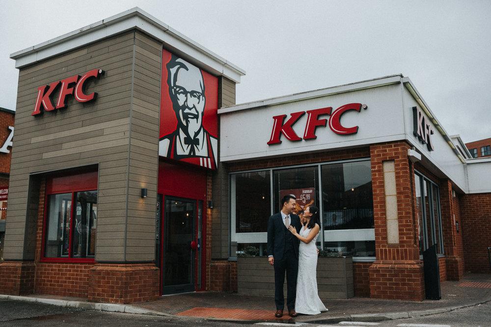 Couple embrace outside KFC.
