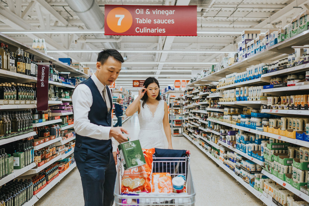 Couple in supermarket shopping wearing full wedding outfits.