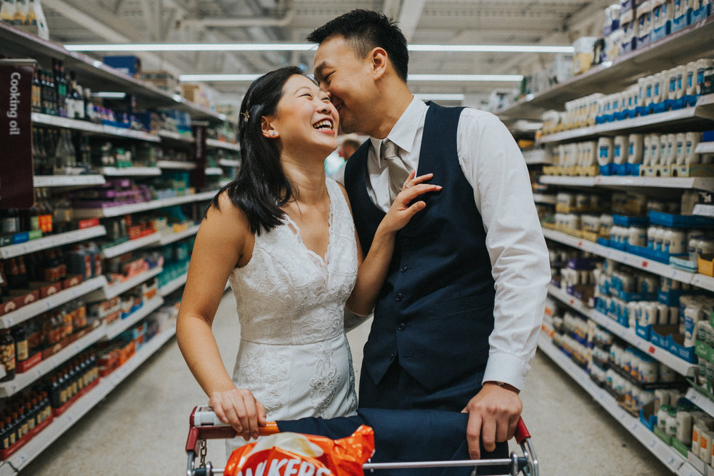 Couple laughing together in the supermarket.
