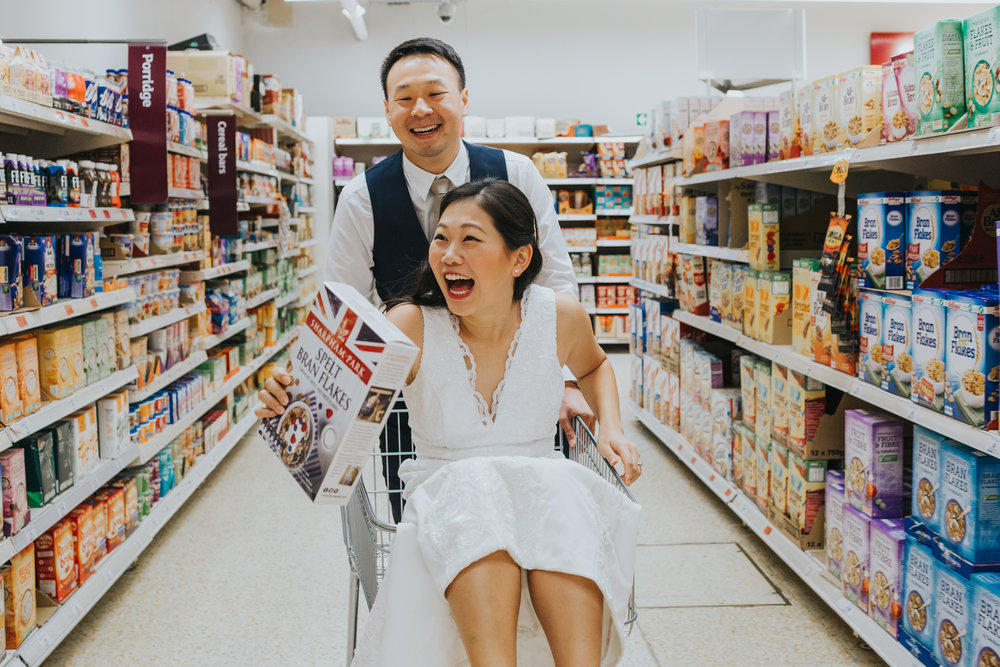 Groom pushes bride around in shopping trolly.
