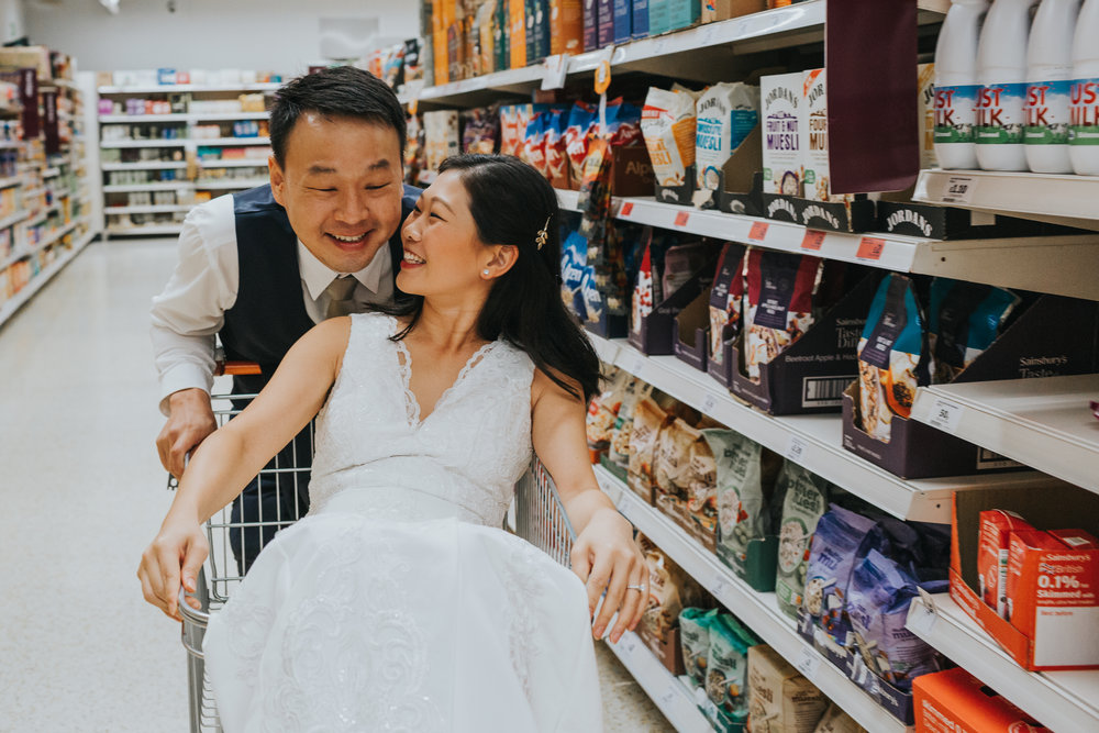 Couple have a moment together as bride sits back in shopping trolley.