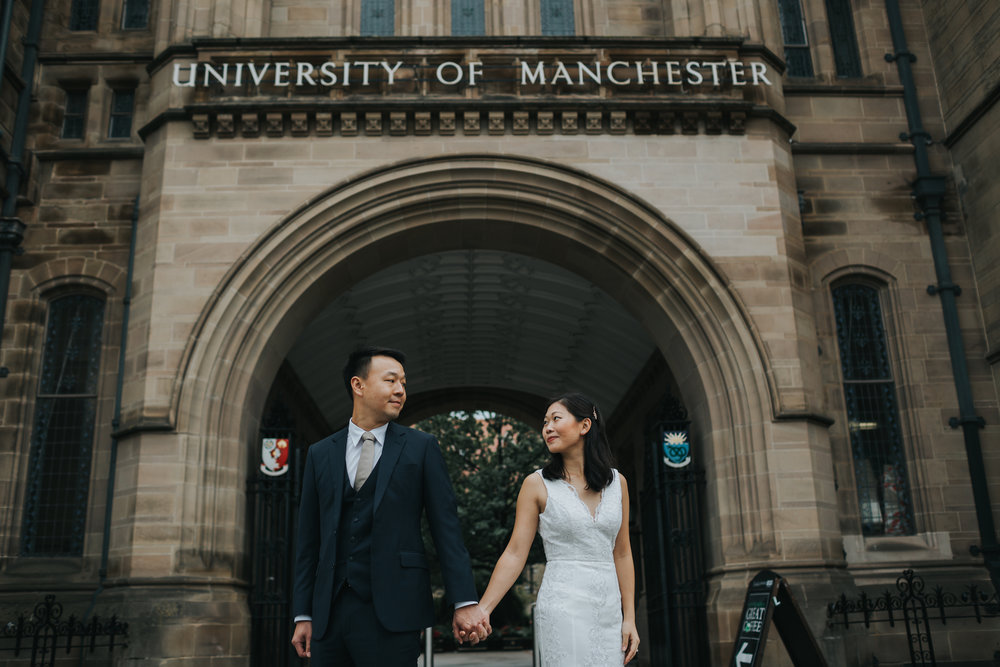 Couple stand together under Manchester University sign.