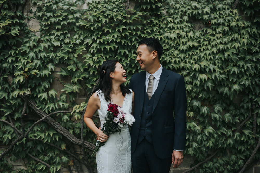 Bride and Groom laughing together in front of a wall full of ivy.