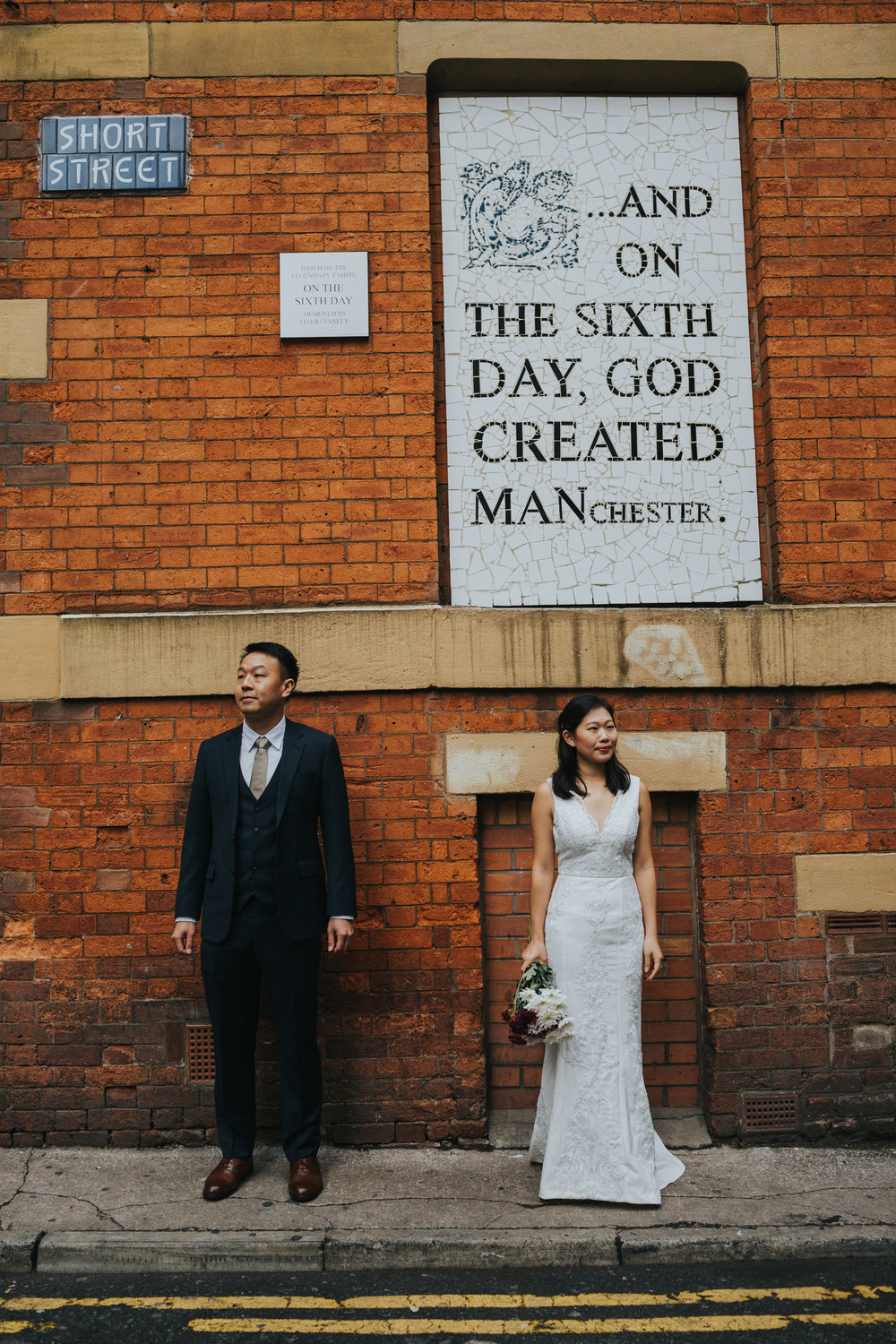 Couple stand together in Wedding gear in front of Aflecks Palace, Manchester.