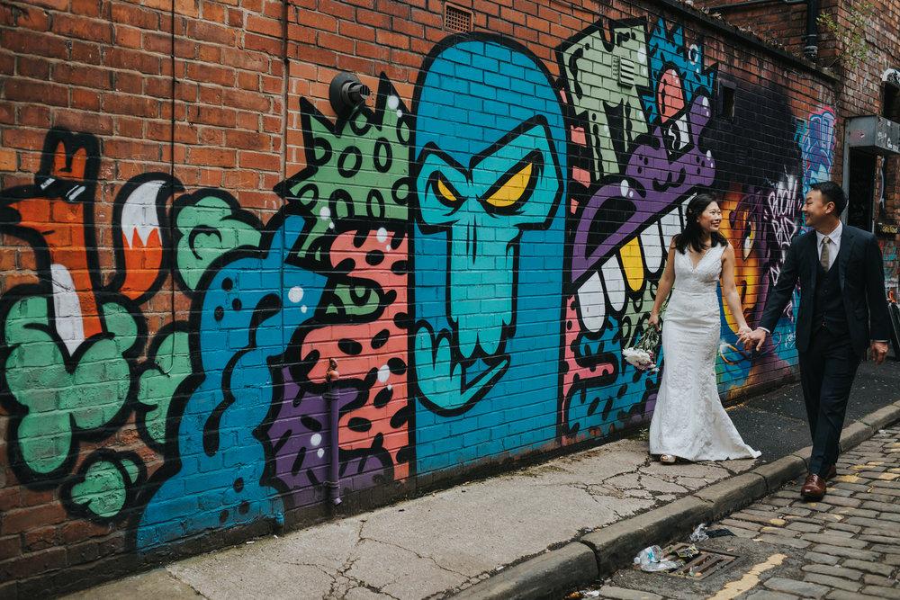 Couple walk along colourful graffiti.