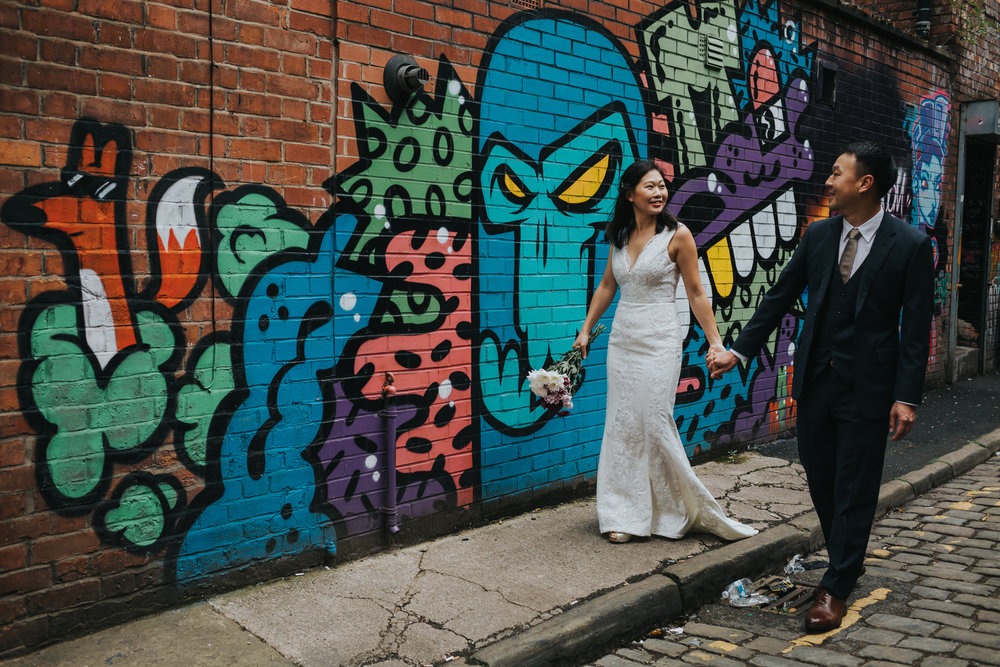 Couple walking together down an alley in Manchester.