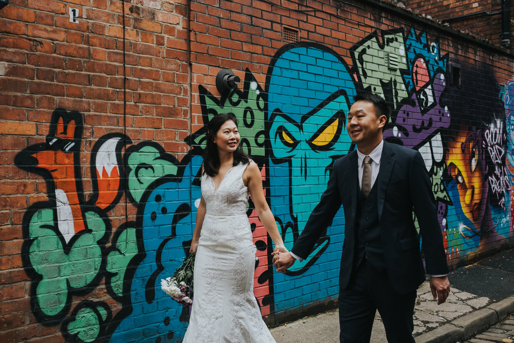 Couple holding hands and walking together in Northern Quarter alley, Manchester.