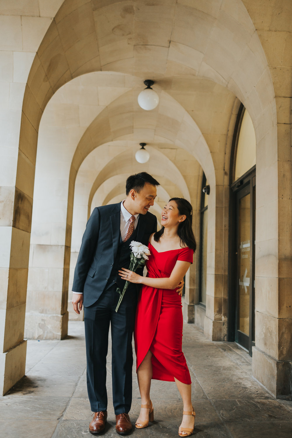 Couple laugh together in the archways of Manchester Town Hall.
