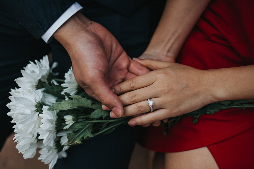 Couple hold hands, close up of engagement ring on Cristal's Red dress and white flowers in the back ground.