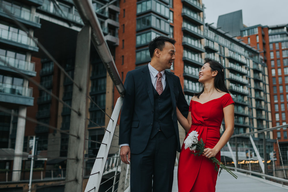 Couple laughing outside Max's old University Halls. Cristal wearing a red dress.