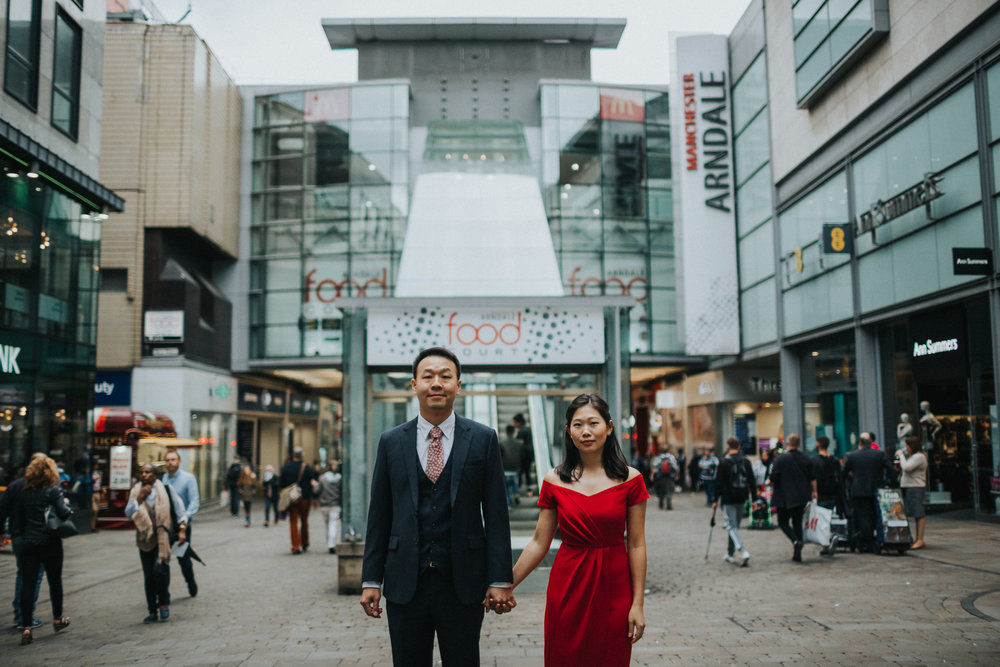 Couple stand together outside Manchester's Food Court, Market Street.
