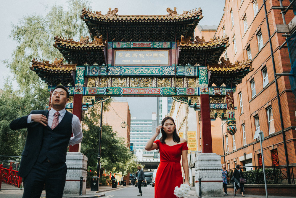 Couple get ready out side China Town Arch Manchester. Focus is on China town arch.
