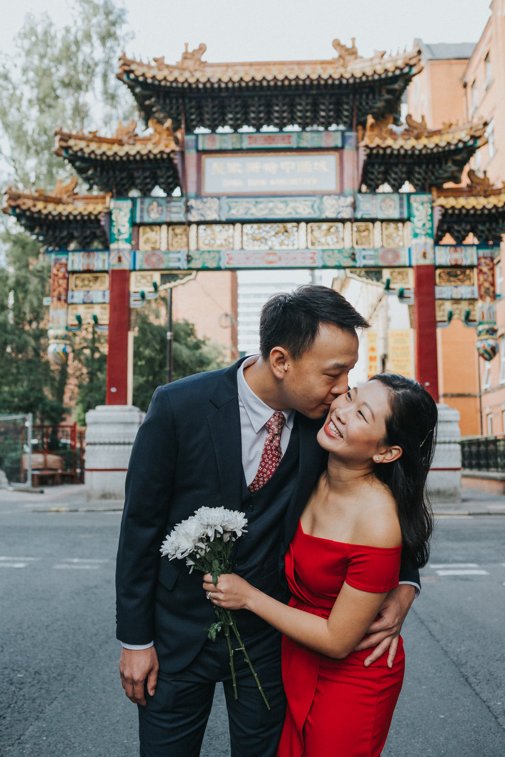 Groom gives his bride a kiss and she beams with delight under China Town Arch.