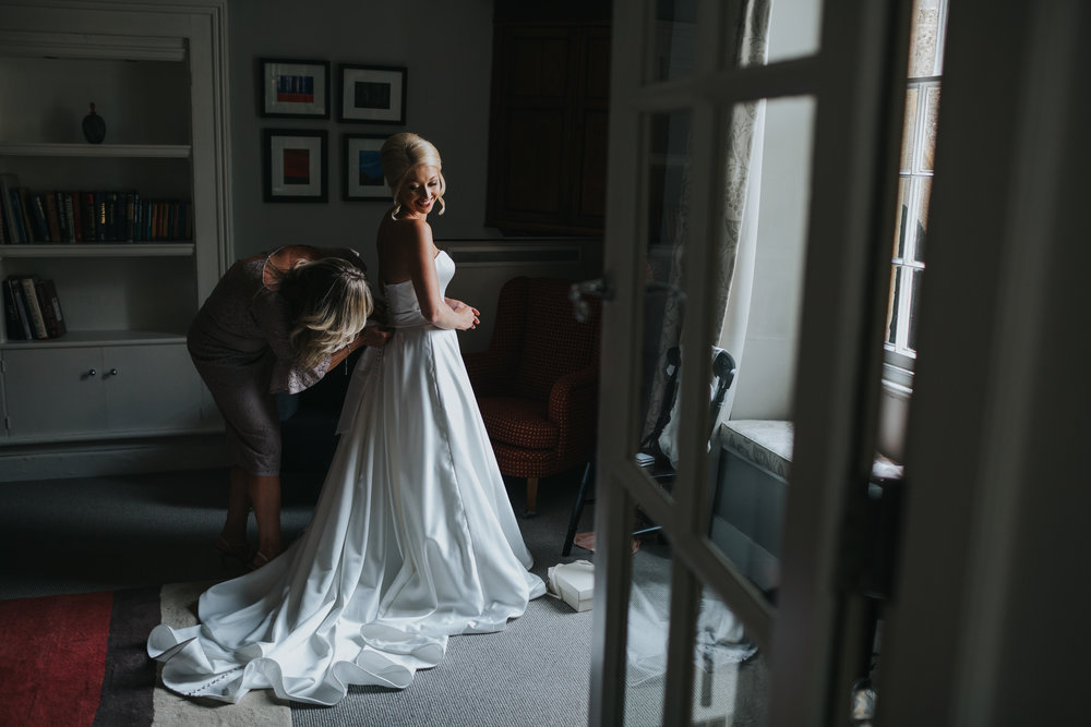 Long shot of Bride having her dress put on in the window light.
