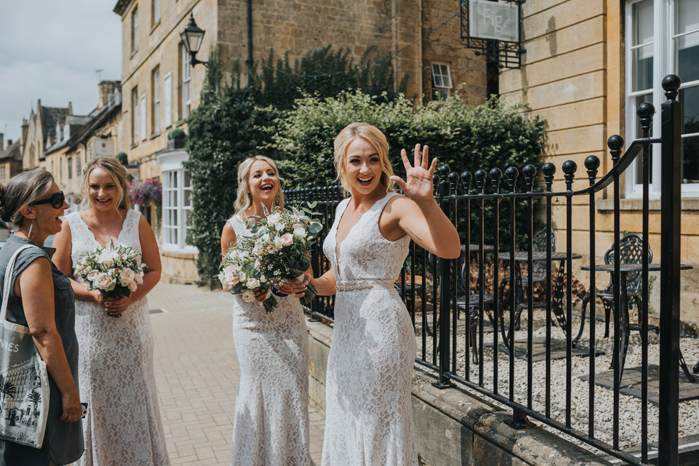 Bridesmaids waving outside The Cotswolds House Hotel.