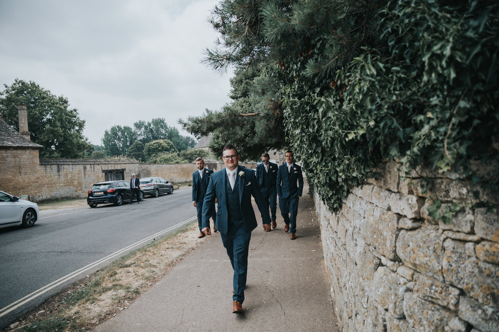 Groom leading his groomsmen to the church.