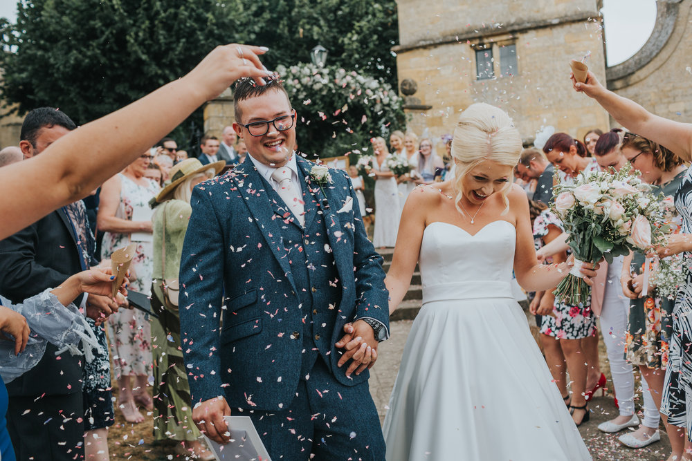Bride and Groom laugh as they have confetti thrown out them outside St James Church, Chipping, Campden.