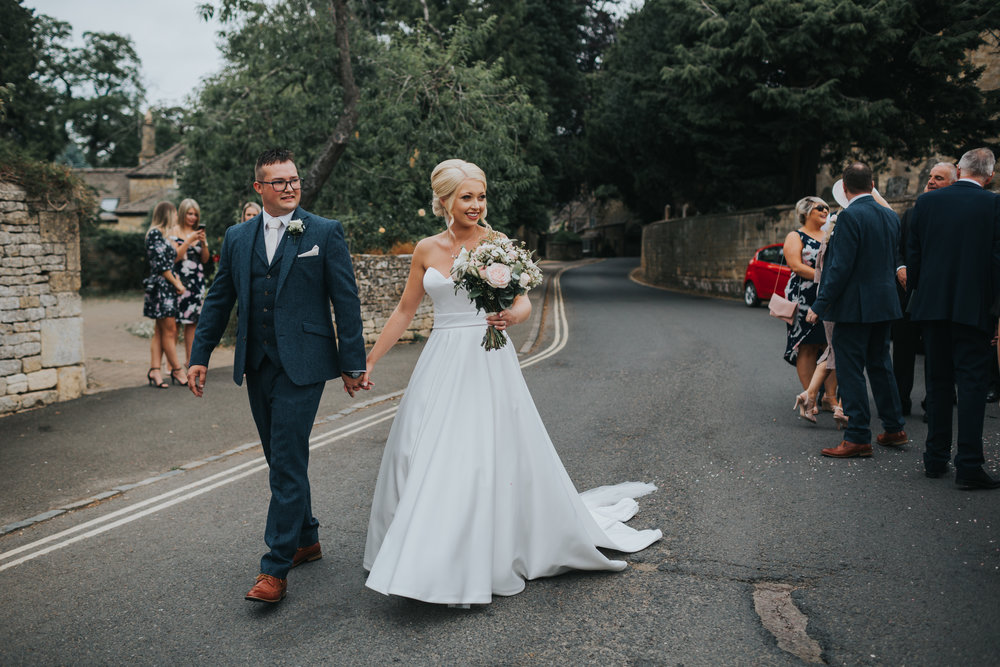 The bride and groom lead their guests away from the church.