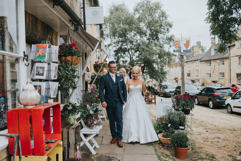 Bride and Groom walk past the local shops together.