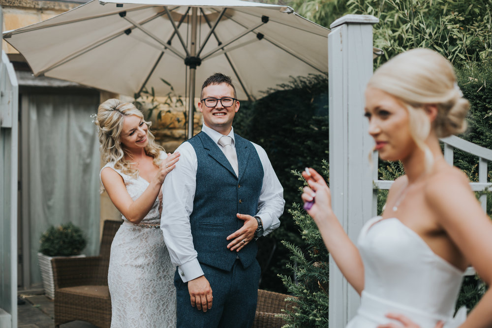 Bridesmaid fixing grooms suit as bride has a fag.