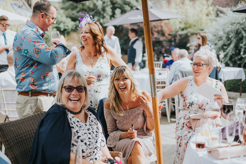 Brides mum laughs with her friends around a table.