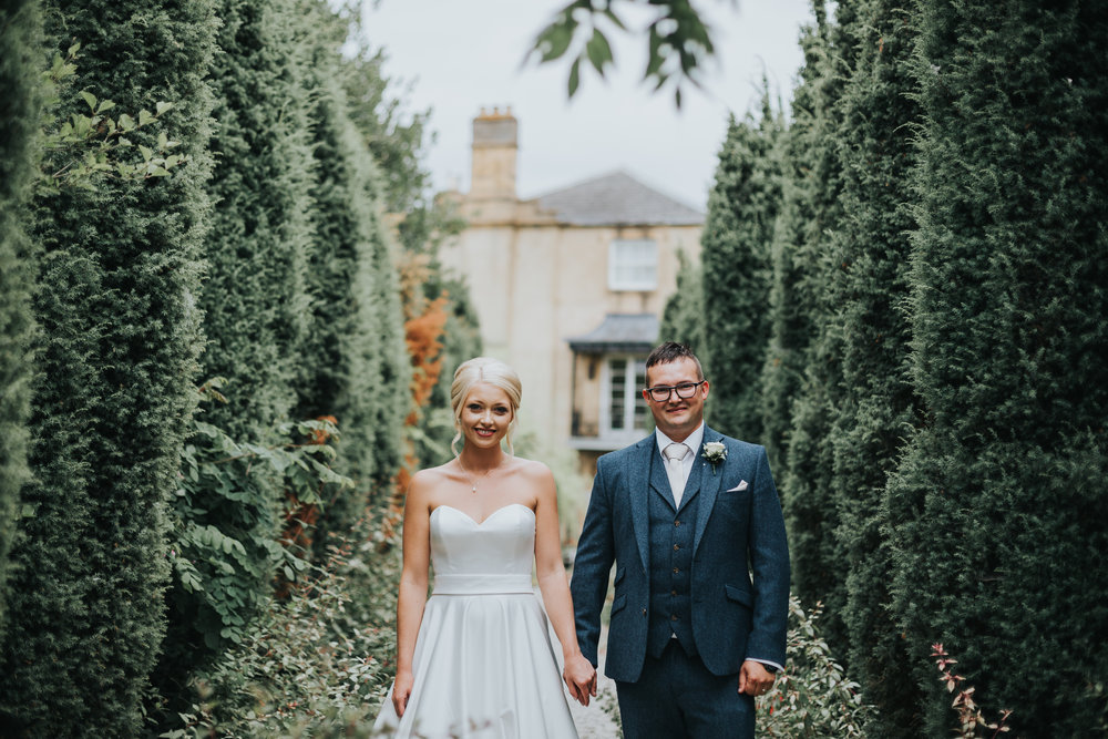 Bride and Groom Stand Side by side in Italian looking tree rowed path.