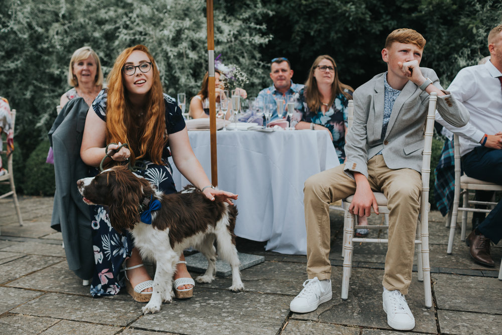 Two red haired children and a dog sit listening to the speeches.