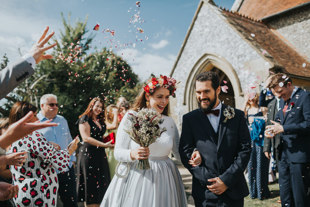 Bride and Groom laugh together and their wedding guests throw dried petal confetti at them at St Mary's Church, Aldworth Village on a beautiful sunny day.
