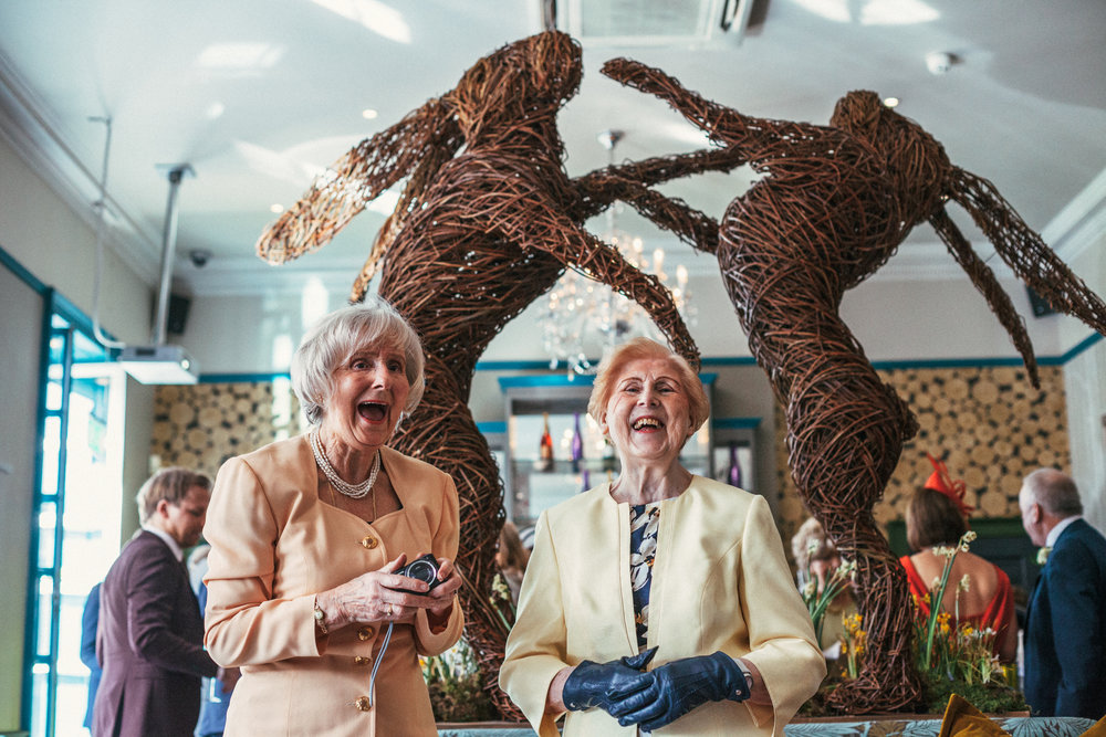 Two old ladies caught laughing together standing in front of 2 big wicca rabbit sculptures at Wedding in Chorlton, Manchester.