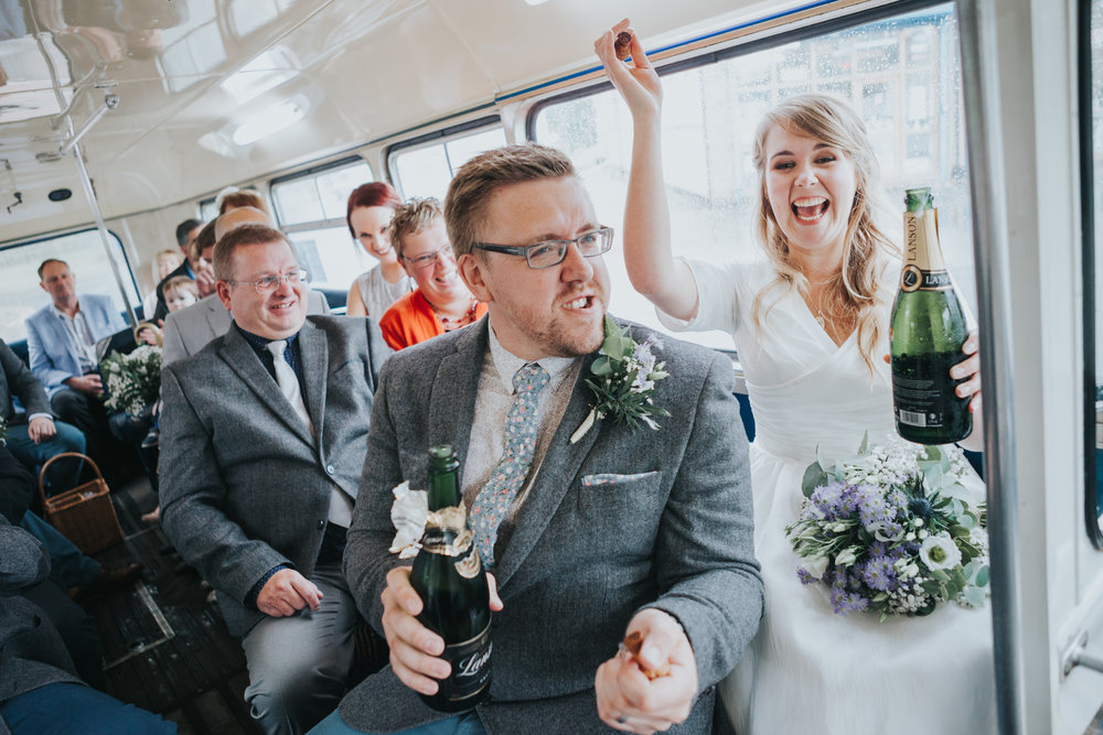Candid photo of the Bride and Groom crack open the fizz on their wedding bus laughing as they make their way to their wedding reception in Manchester City Centre.