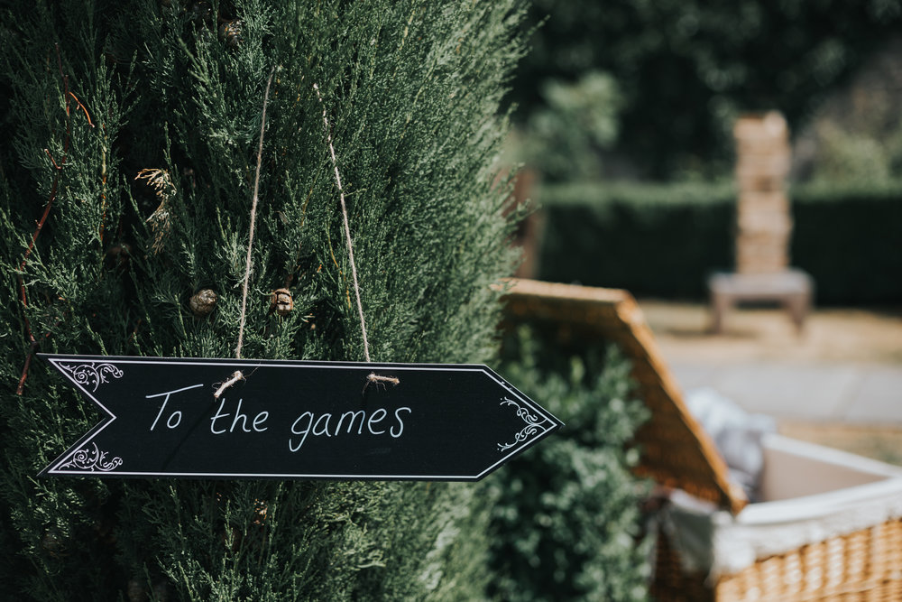 To The Games chalk board sign hanging of a tree at an outdoor wedding.