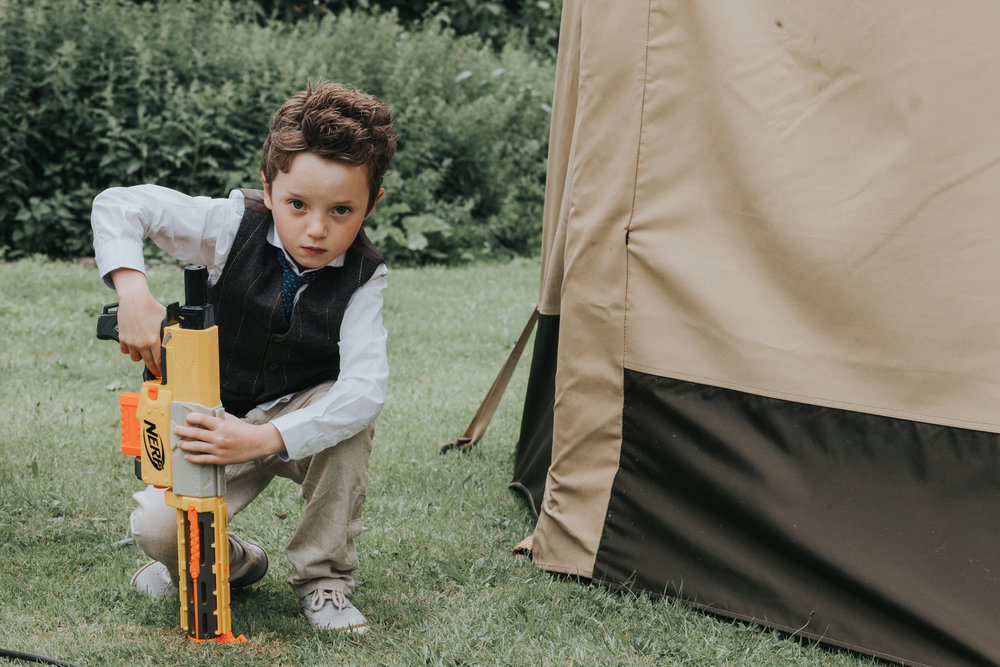 Child crouches down behind tipi, holding his water gun ready to wreak havock on unsuspecting wedding guests.