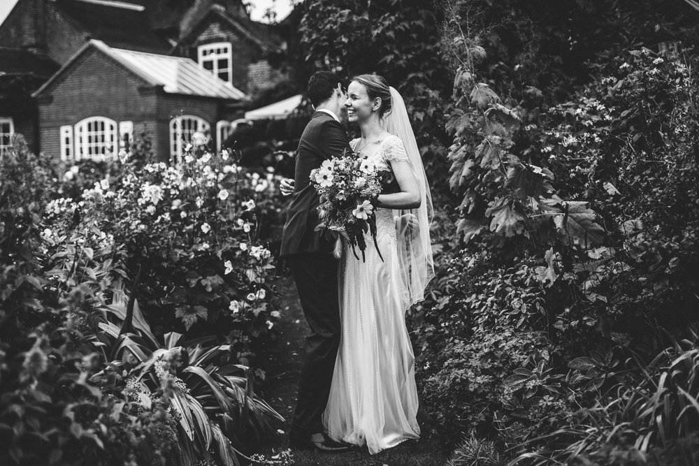 Couple laugh together on their wedding day at Goldstone Hall, Market Drayton. Photograph in black and white.