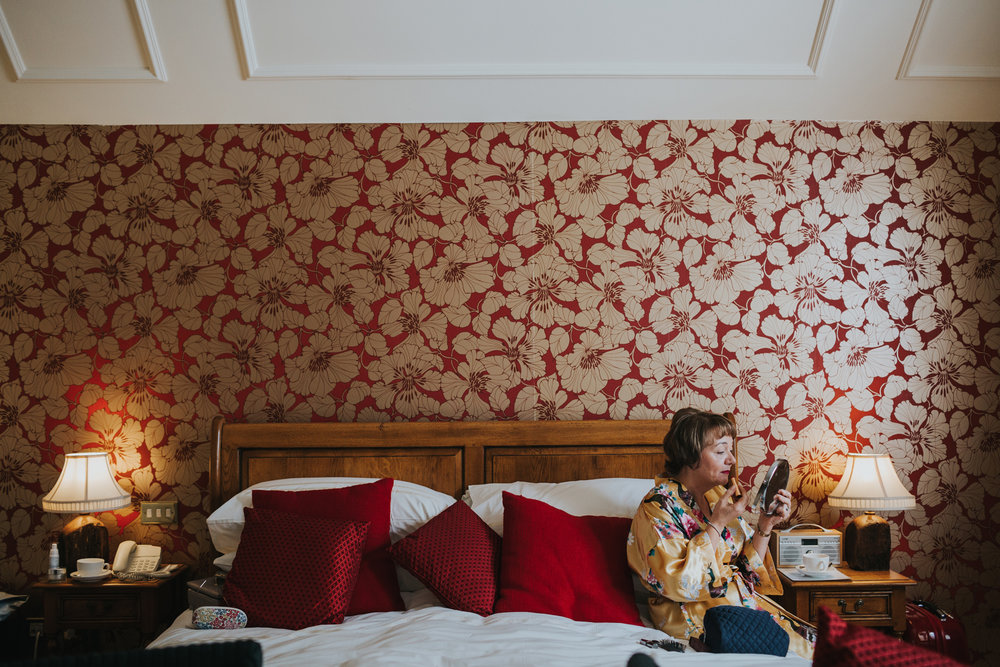Mother of the bride sits on a bed putting on her lipstick in front of a wall of very loud red and gold floral wall paper framed by two matching lamps.