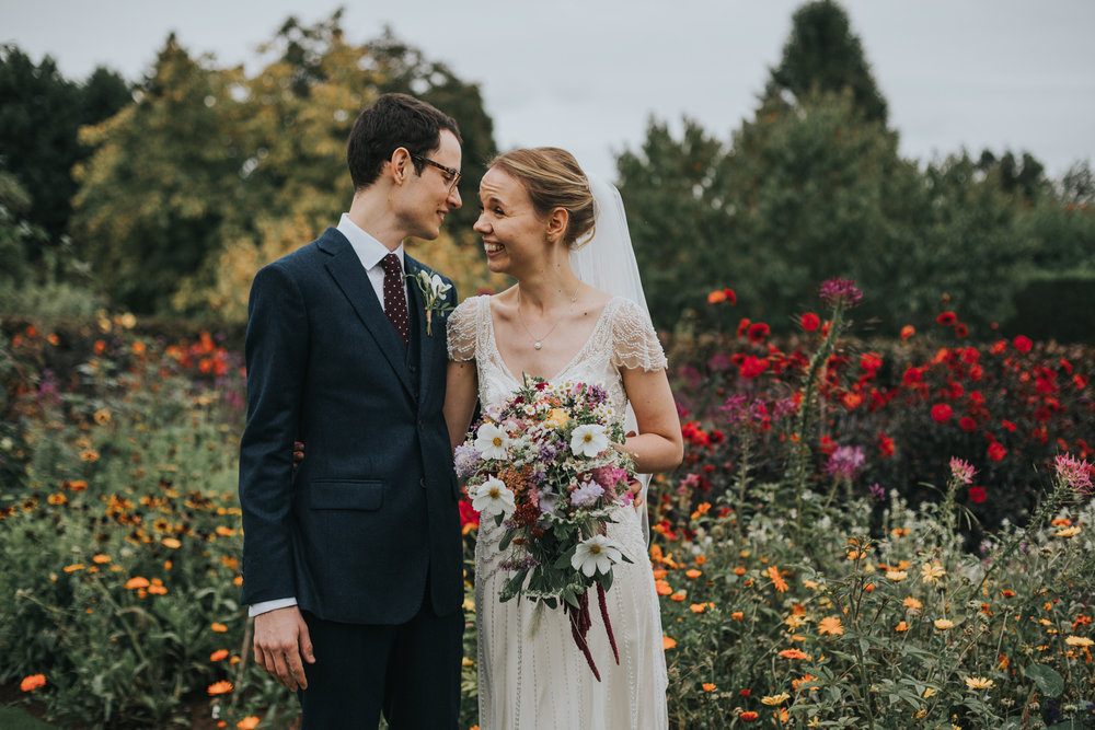Bride and Groom stand with a sea of colourful wild flowers together at Goldstone Hall, Market Drayton.