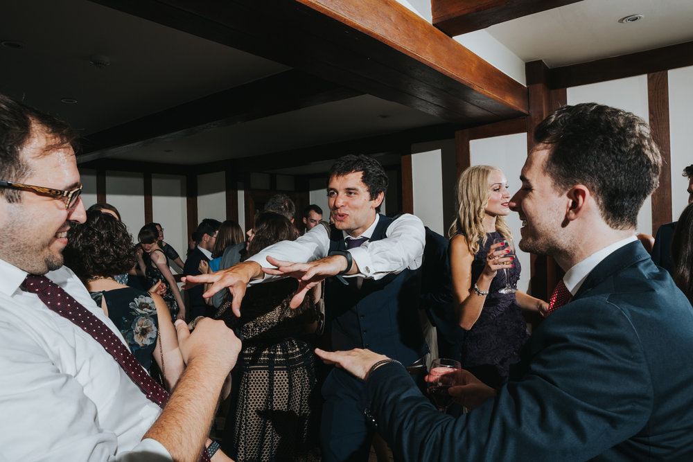 Male wedding guests throw out some stretchy arm dance moves.