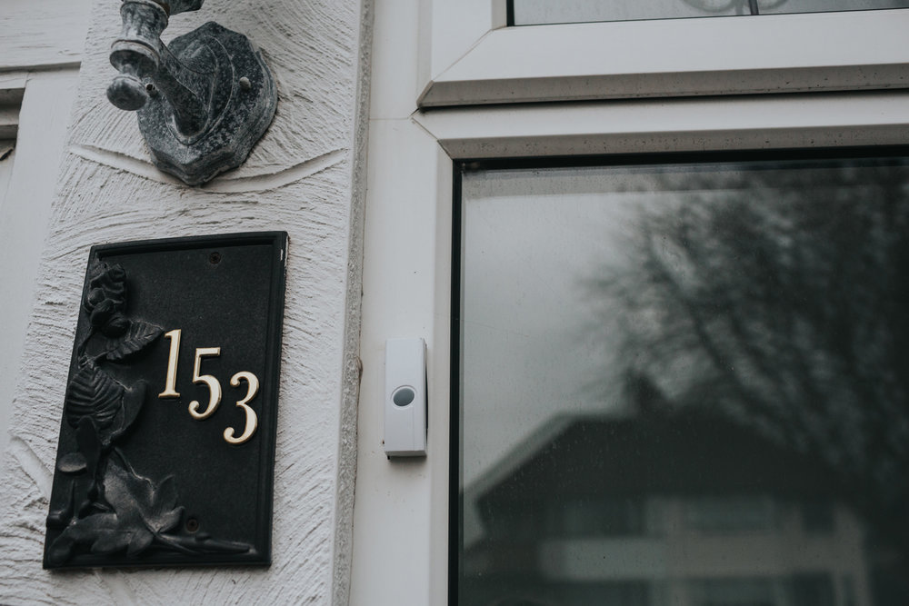 A photograph of the door number with a reflection of the opposite house in the window.