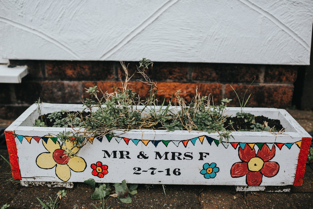 "Plant pot decorated with ""Mr and Mrs F"" outside the family home."