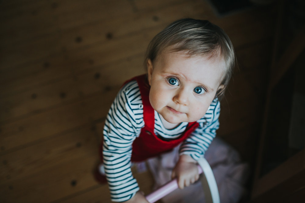 Little girl looks up at the camera with a curious look. It's her first birthday.