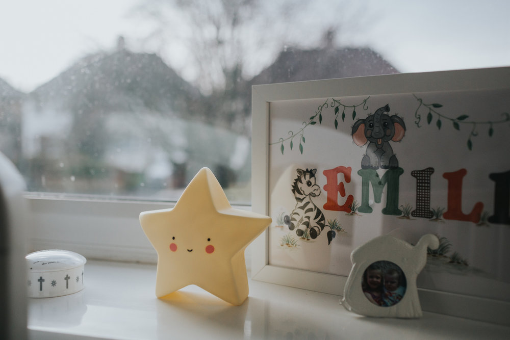 A smiling star toy stands on a windowsill of a child's room, the view of the liverpool street outside can be seen.