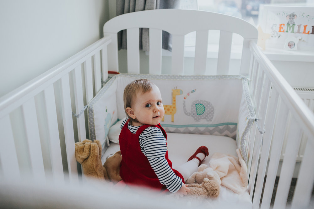 Child looks back at the camera as she sits in her cot with her cuddly toys.